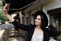 A beautiful girl dressed in a stylish white dress, a black jacket and a black hat is standing near the marble coffee table and a w Stock Photos