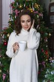 A beautiful girl dressed in a white sweater is standing among Ch royalty free stock image