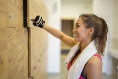 Beautiful girl in the dressing room at the gym opening her locke. R while smiling Royalty Free Stock Photography