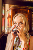 Beautiful girl drinking beer from the glass cup. Royalty Free Stock Photo