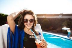 Beautiful girl drinking cocktail, lying on chaise near swimming pool. Beautiful brunette girl smiling, drinking cocktail, lying on chaise near swimming pool stock photo