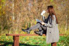 Beautiful girl drinking coffee in autumn park outdoors Stock Photos