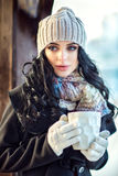 Beautiful girl is drinking a coffee from big white cup. Outside photo shoot. Winter. A girl is in warm clothes and with hat on head. Nice make up and curly Royalty Free Stock Photo