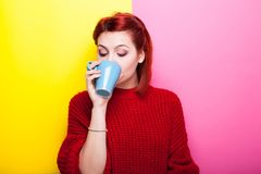 Beautiful girl drinking coffee from a blue mug. On two colored background in yellow and pink Stock Photos