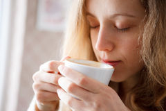 Beautiful girl drinking coffee. Cup of hot beverage Royalty Free Stock Photos