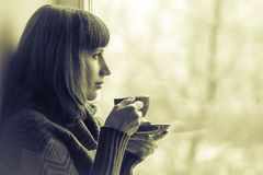 Beautiful girl drinking coffee near window. Toned Image Royalty Free Stock Images