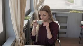 Beautiful girl drinking coffee and relaxing in cafe. Woman with cup of coffee stock video footage