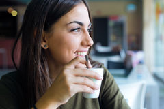 Beautiful girl drinking coffee sitting indoor in urban cafe. Royalty Free Stock Images