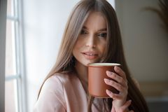Beautiful girl is drinking coffee and smiling while sitting at the cafe stock photography