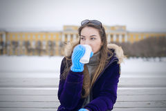 Beautiful girl is drinking coffee in the street. Stock Photography
