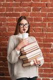 Beautiful girl drinking coffee-to-go on books Royalty Free Stock Photos