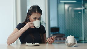 Beautiful girl drinking coffee and using phone in a cafe stock video footage
