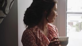 Beautiful girl drinking coffee on the windowsill 1 stock video