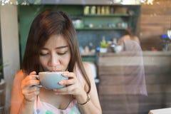 Beautiful girl drinking hot coffee or tea in coffee cafe Stock Photos