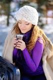 Beautiful girl drinking hot hour outdoors in the winter Royalty Free Stock Photos