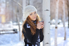 Beautiful girl drinking hot tea in winter outdoors.  Stock Photo