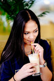 Beautiful girl drinking ice mocha shake in a cafe.  stock photos