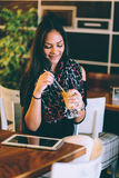 Beautiful girl drinking ice mocha shake in a cafe royalty free stock image