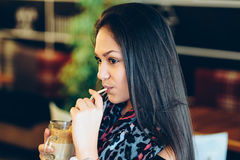 Beautiful girl drinking ice mocha shake in a cafe.  royalty free stock image
