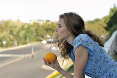 Beautiful girl is drinking juice through a straw from an orange Royalty Free Stock Photos