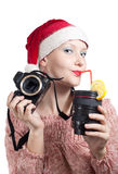 Beautiful girl drinking from lens cup isolated. Beautiful girl drinking from lens cup holding DSLR camera without lens in Christmas hat isolated on white Royalty Free Stock Photo