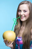 Beautiful girl drinking pomelo juice through a straw Royalty Free Stock Image