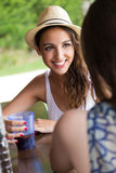 Beautiful girl drinking in the pool bar with friend. Royalty Free Stock Photo