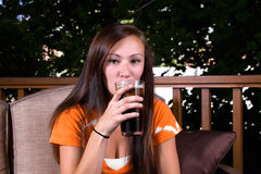 Beautiful Girl Drinking Soda in the Patio Royalty Free Stock Photography