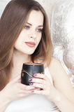 Beautiful Girl Drinking Tea or Coffee. Beauty Woman with Cup of Hot Beverage. Enjoying Coffee. Warm Pastel Colors Stock Image