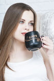 Beautiful Girl Drinking Tea or Coffee. Beauty Woman with Cup of Hot Beverage. Enjoying Coffee. Warm Pastel Colors Stock Photography