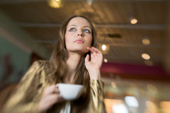 Beautiful Girl Drinking Tea or Coffee in Cafe Royalty Free Stock Photography