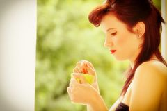 Beautiful Girl Drinking Tea or Coffee Indoor. Green Blurred Background Royalty Free Stock Photos