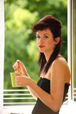 Beautiful Girl Drinking Tea or Coffee Indoor. Green Blurred Background Royalty Free Stock Images