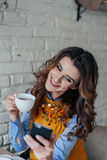 Beautiful girl drinking tea and working with phone Stock Image