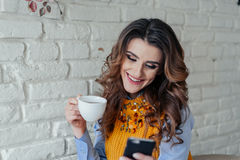 Beautiful girl drinking tea and working with phone Royalty Free Stock Photo