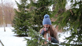 Beautiful girl drinking from a thermos near trees stock video