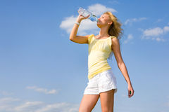 Beautiful girl drinking water against blue sky.  Royalty Free Stock Photo