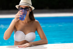 Beautiful girl drinking water at the swimming pool. Stock Photography
