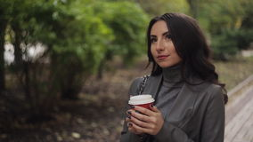 Beautiful girl drinks coffee in cold autumn park stock video footage