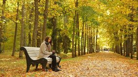 Beautiful girl drinks coffee from a cup while sitting on a bench in autumn park. Glamour girl drinks coffee from a red cup and smiles on a bench in a picturesque stock video