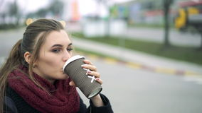Beautiful girl drinks coffee at a gas station. 4k stock footage