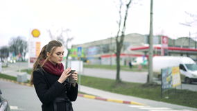 Beautiful girl drinks coffee at a gas station. 4k stock video