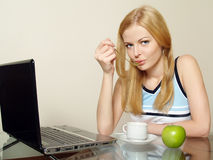 The beautiful girl drinks coffee about the laptop Stock Photos