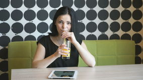 Beautiful girl drinks orange juice indoors. Beautiful girl aged 20s drinks orange juice and watches photos with a digital computer tablet indoors stock video footage