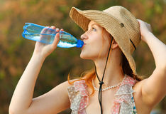 Beautiful girl drinks water. Beautiful red-haired girl in straw hat drinks water from bottle stock image