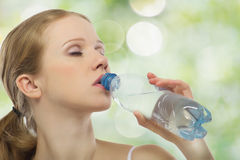 Beautiful girl drinks water from a bottle Stock Image