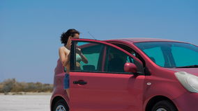 A beautiful girl driving red Nissan Note at the salt lake. stock footage