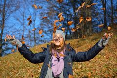 Beautiful girl drop up leaves. In autumn forest Stock Image