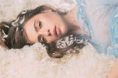 Beautiful girl drowning in soft bed. Drowsy young lady falling asleep, resting on downy white feathers, coziness concept.  stock photos