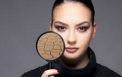 Beautiful girl with dry skin problem close up concept. Beautiful girl holding magnifier close up concept with skin problem dry skin stock photography